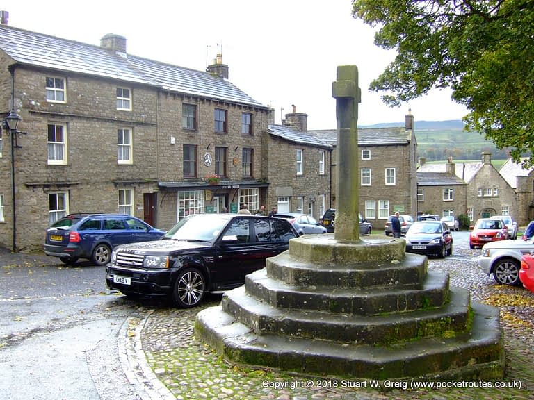 Memorial cross in the village square, beside the church